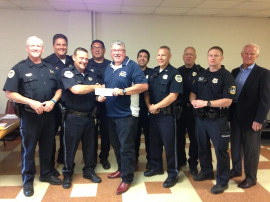 Members of the Des Moines Police Department present Craig Phinney of Cops Against Cancer with a donation check. The organization uses grants and donations to help people who are dealing with a cancer diagnosis.