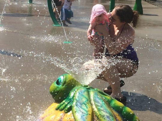 A local mom shows her infant daughter one of the interactive features at the White House splash pad on Saturday, June 17.