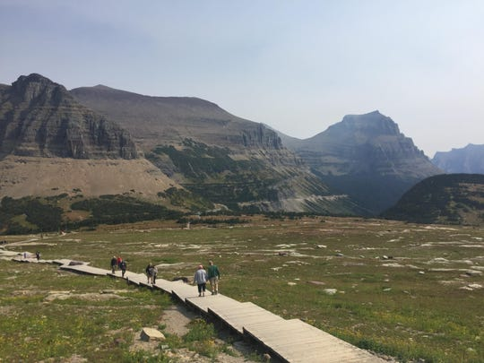 Hikers follow the Hidden Lake trail at Glacier National Park in Montana. Wildlife officials are asking people who are traveling near the park to report sightings of animals crossing the road. Park officials and the U.S. Geological Survey want to know where animals are crossing U.S. Highway 2.