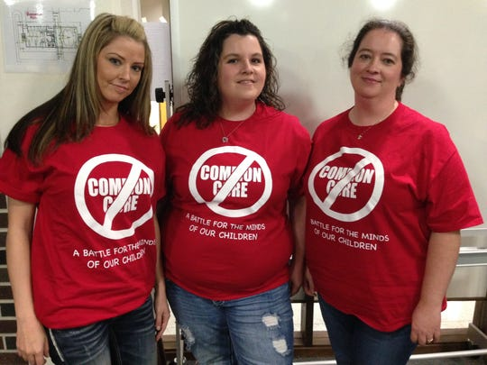 """Rapides parents Amy Creel (left), Brittany Cloud and Daphne Pace wear T-shirts reflecting their stance against the Common Core State Standards to a Rapides Parish School Board meeting Tuesday. The red shirts read """"A battle for the minds of our children."""""""