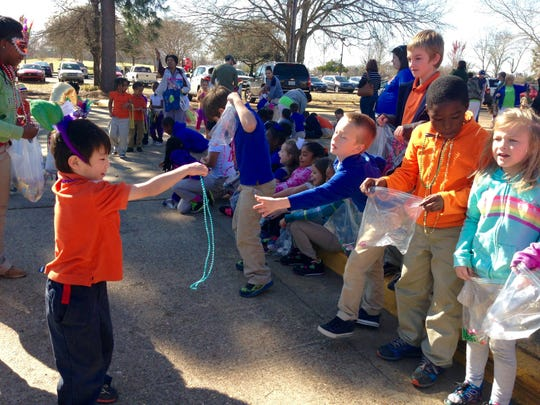 "A kindergartener at J.B. Nachman Elementary throws Mardi Gras beads to fellow students at the annual ""Krewe of Kindergarten"" parade Thursday."