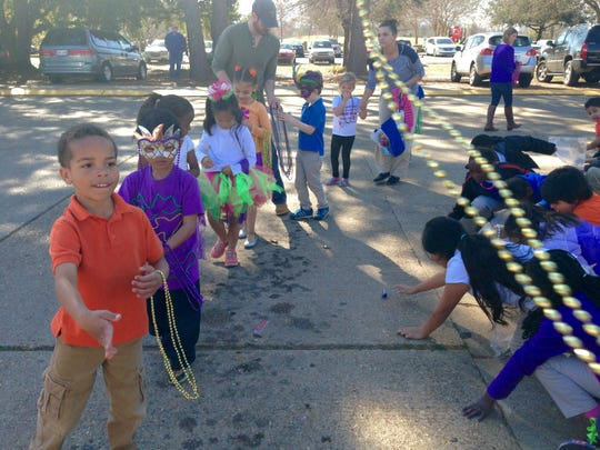 "Kindergarten students at J.B. Nachman Elementary throw Mardi Gras beads to fellow students at the annual ""Krewe of Kindergarten"" parade Thursday."