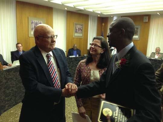 Larry Spottsville (right), director of Juvenile Services for the 9th Judicial District Court, receives an emotional congratulations from Bud Paul, his predecessor, on Monday as Judge Patricia Koch looks on. Spottsville was honored by the Rapides Parish Police Jury for his 35 years of service in juvenile probation.