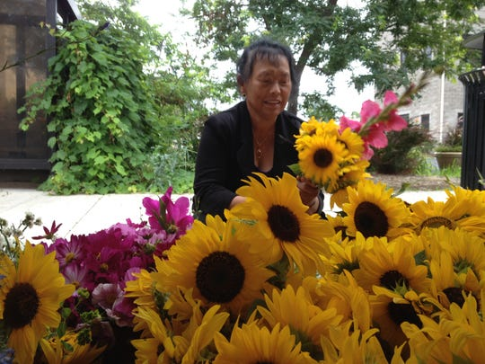 Ying Yang of Oshkosh prepares one of dozens of one-of-a-kind floral bouquets she'll display for farmers market customers in Oshkosh.