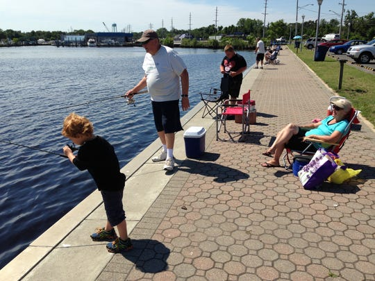 SOUTH TOMS RIVER — Kenneth Probst, 67, of Forked River, fishes for snapper blues in the Toms River with grandsons Cameron McMillan, 5, (left), and Jake Paolo, 11, (right), while Ken's wife Mary, 66, watches. Probst said they can't swim in the bay anymore because of the stinging jellyfish.