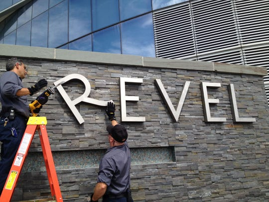 Revel employees remove letters from a sign at the casino on Sept. 1 in Atlantic City.