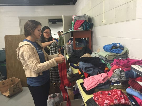 For Martin Luther King Jr. Day of Service, Warren Wilson College students volunteered at Hall Fletcher Elementary. From left, college juniors Austin Fust and Jasmine Woo organize donated clothing for the school's clothing closet to help students in need.