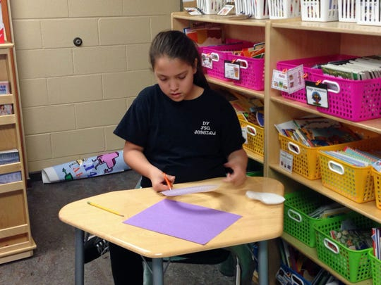 Cherokee tribe member Haley Smith, 11, works on an English assignment at New Kituwah Academy in Cherokee in February. On this particular day, Haley and her classmates were learning about idioms related to Valentine's Day. With fewer than 300 native Cherokee speakers remaining in North Carolina, tribe members hope to preserve their language and culture through the small school where their children are immersed in their people's native tongue.