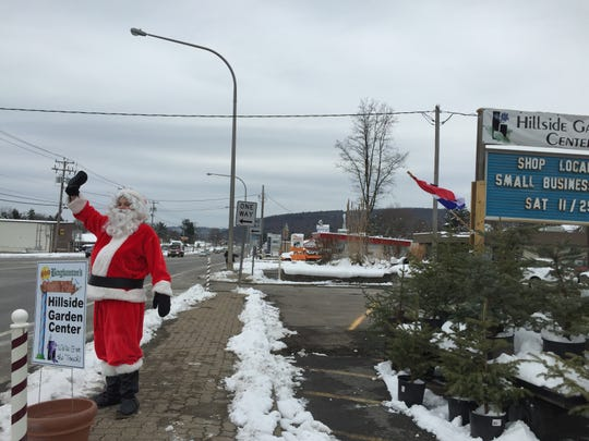 Santa Claus waves at traffic outside Hillside Garden