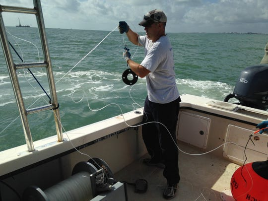 Eric Reyier, a biologist at Kennedy Space Center, handles a longline fishing gear. He has been conducting fish-tracking research of red drum, sharks and other fish off of Cape Canaveral.