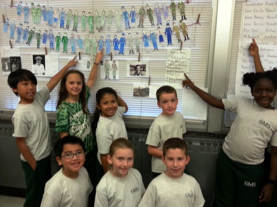 Third-graders in Cathleen Allegro's history class at St. Matthias School, Somerset section of Franklin, remembered Veterans Day with an honor wall of names of veterans from the students' families. Front row, left to right, are Aidan Jarvis, Kristin McNally and Anthony deLutio; back row, left to right, are Aidan Angeles, Adriana Liberti, Maya Matthews, Trevor Lavelle and Feyintoluwa Olajitan.