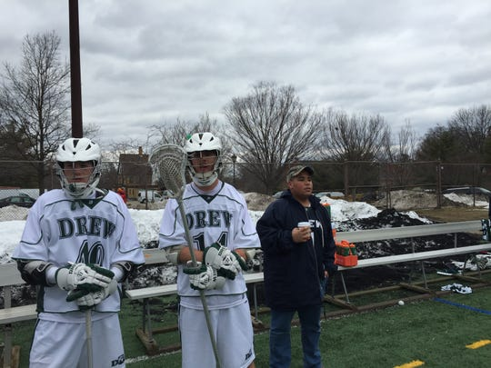 Midfielder Colin Kreder of Flemington and defender Charlie Hammel watch the Drew men's lacrosse game with 13-year-old Anthony Pernell of Plainfield, a Team IMPACT match.