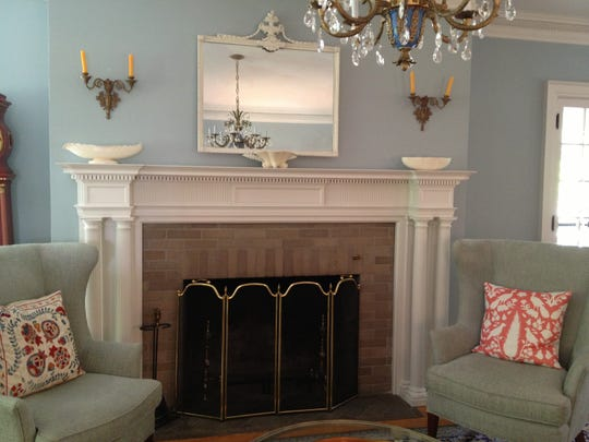 Wing chairs flank the fireplace in the living room.