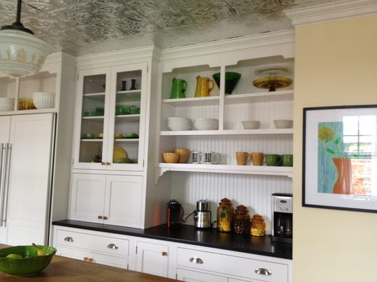 The renovated kitchen with clean white cabinetry, a new tin ceiling and a long, rustic, wooden table.