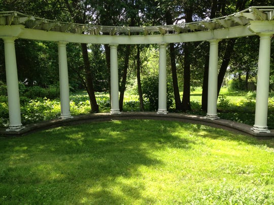 Sun filters through the trees onto the curving pergola in the back yard of the Zweber home.