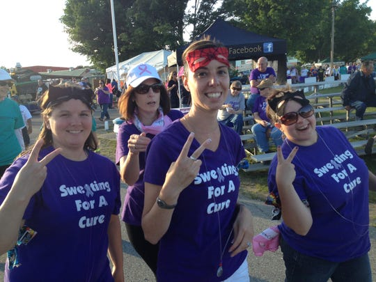 Membes of Team Sweating For a Cure give victory signs in Friday's Relay For Life.