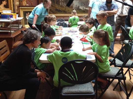 Vermont Education Secretary Rebecca Holcombe, bottom left, watches school children complete a project.