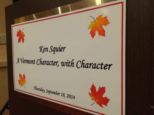 A placard decorates the podium in a ballroom at the Hilton Burlington hotel on Thursday night ahead of a surprise party and film showing in honor of Ken Squier of WDEV.
