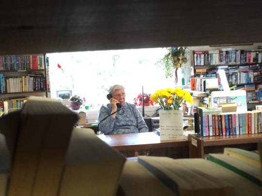 Bev Brown talks on the phone at the Book Worm's Exchange in South Burlington on Tuesday.
