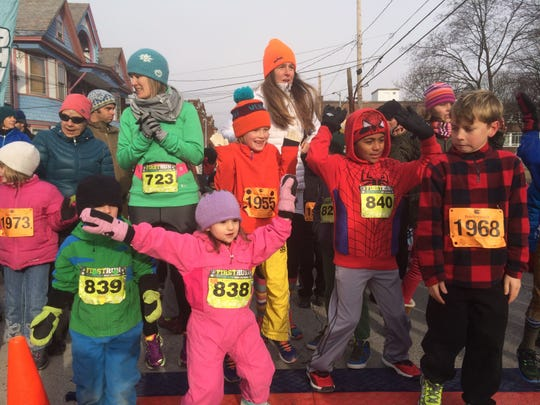 Young runners stay warm before their half-mile run in Burlington, part of the annual First Run events on New Year's Day.