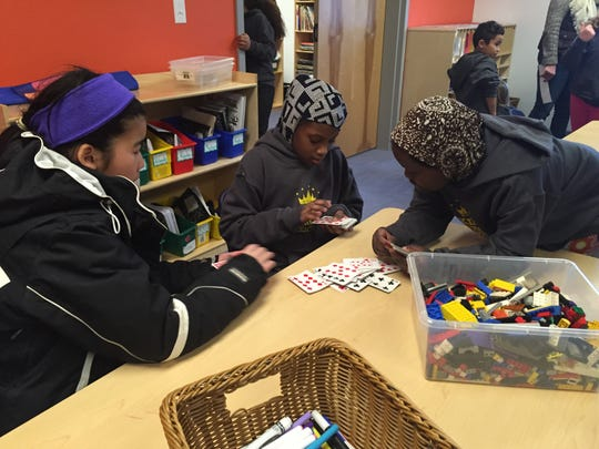 Children play slapjack after school at the newly renovated King Street Center. From left is Esther Htwe,11, Flastine Jafar, 10, and Halima Hussein, 10.