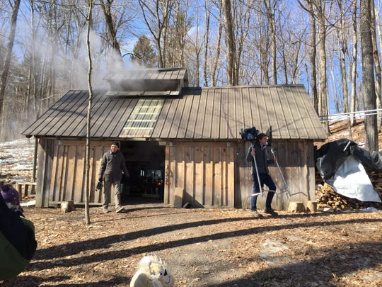 "A production crew from the PBS show ""Ask This Old House"" was at Shelburne Farms Tuesday to film an episode about maple sugaring. Here members of the crew exit the sugar shack."
