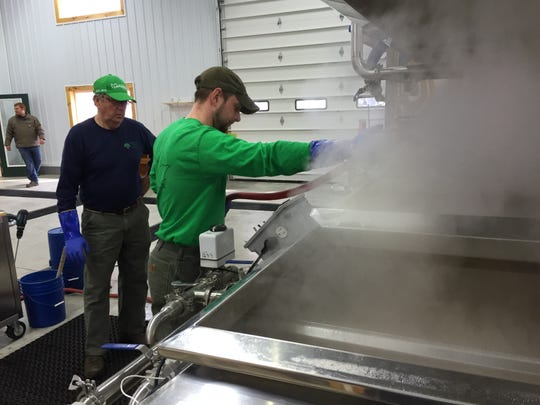 Kyle Branon and his uncle, Shaun Branon, boil sap at Branon Family Maple Orchards in Fairfield on Maple Open House Weekend.