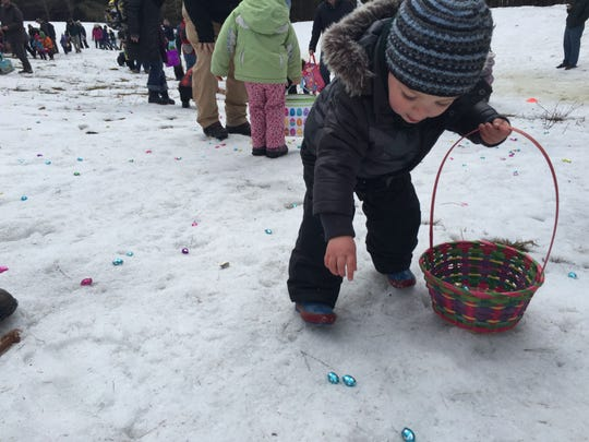 Cole Jones, 2, of Montpelier spots a chocolate egg in the snow covered field in Montpelier's Hubbard Park. His mother cheered him on as he filled up his Easter basket.
