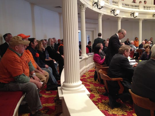 Observers wearing orange, commonly understood to be a symbol of gun rights in political debates, listen as Rep. Tom Burditt, R-West Rutland, challenges a gun-related bill during debate at the Statehouse in Montpelier on Thursday.