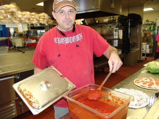 Owner Marty Ralston stirs his New York-style sauce at Crowtown Pizza in Coshocton.
