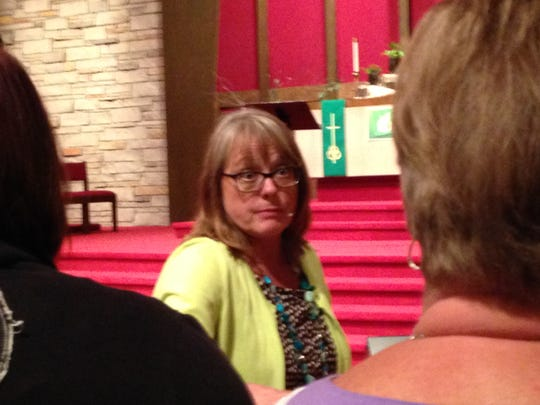 Joan Becker speaks to family members before taking the stage Tuesday night at Ankeny First United Methodist Church.