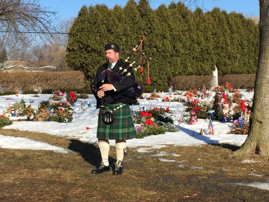 A bagpiper plays for the funeral of the baby named Henry Alexander Macomb by morgue workers March 11 at Resurrection Cemetery in Clinton Township.