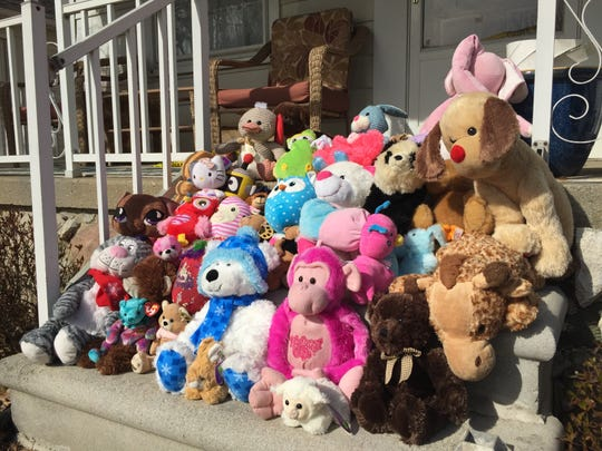 A makeshift memorial of three dozen stuffed animals sits on the front steps of the Cushing home in Eastpointe where Christie Fradeneck, 37, and her two children, Celeste, 2, and Timothy, 8, were found dead April 13, 2015.