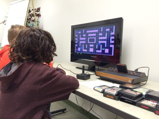 """Kids play """"Pac-Man"""" on an old-fashioned Atari at the Home Video Arcade Experience at the Fond du Lac Public Library."""