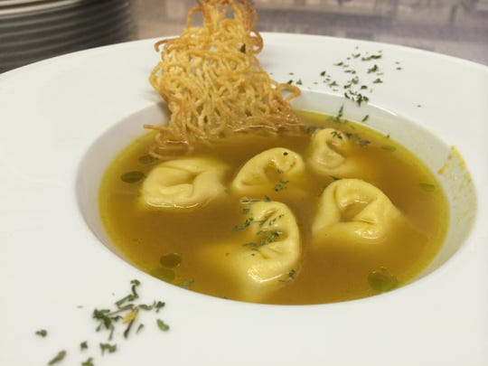Pumpkin consomme with braised pork and chicken tortellini and drops of basil oil from Enzo's in Bonita Springs.