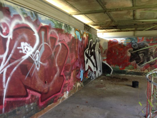 Grafitti covers the murals that once lined the Cypress Knee Museum's walls.