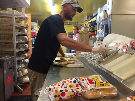 Nick Caruso prepares a burger as his wife, Rachel, waits at Caruso's Eats and Treats in south Fort Myers.