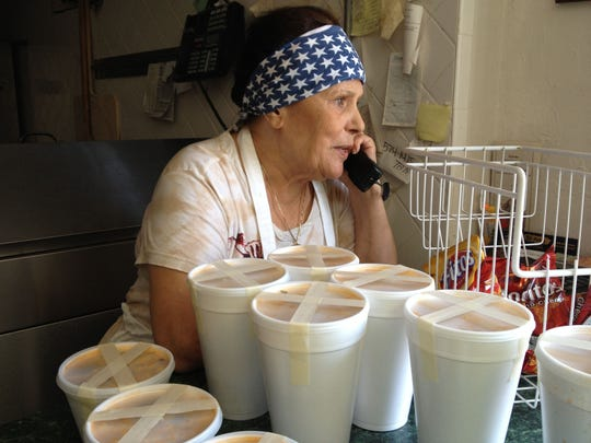 """In this 2013 photo, Rosaria """"Mama"""" Leone takes an order at Leone's Italian Food & Specialty in Cape Coral as quarts of her pasta fagioli await pickup on the counter. Leone's closed Saturday after 41 years in business."""