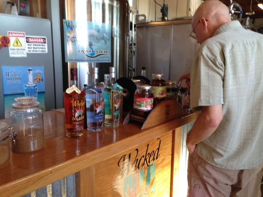 A tour participant examines the display of rums and raw ingredients during a tour at the Wicked Dolphin Artisan Rum distillery in Cape Coral.