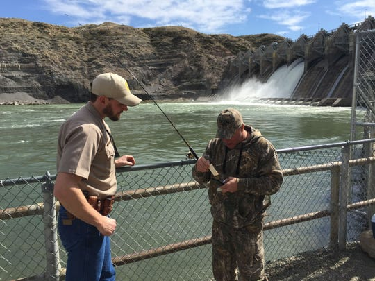 Jay Meeks shows his fishing license to Brett Logan, an FWP game warden. A big part of the job, Logan says, is checking fishing licenses at public access sites.