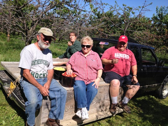 Two couples from Denmark shared a wagon after picking pails of cherries at Paradise Farms, Brussels, Thursday morning. From left, Gary and Orlane Moore and Eric and Sharon (back) Treml had apparently never met. The camaraderie and good-tasting cherries outshined the ailing cherry tree behind them.