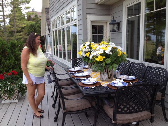 Brenda Gilmore, Plainfield, Ill., admires the outdoor table setting on the deck of Peggy and Tom Phillips, 4712 Bark Road, Sturgeon Bay. The Phillips' home was one of four featured in this year's 54th annual House & Garden Walk.