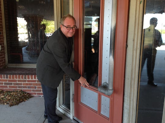 Michael Schwantes, president of Creative Business Services, wipes the cobwebs off the door of the former Applebee's that has been shuttered for more than four years at 129 N. Madison Ave., Sturgeon Bay.