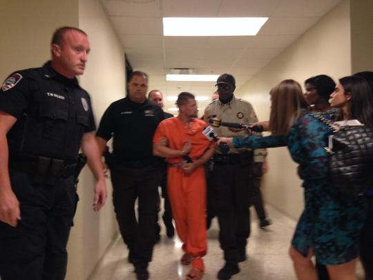 Murder suspect Joseph Oberhansley is escorted by officers in Clark Circuit Court on Monday.