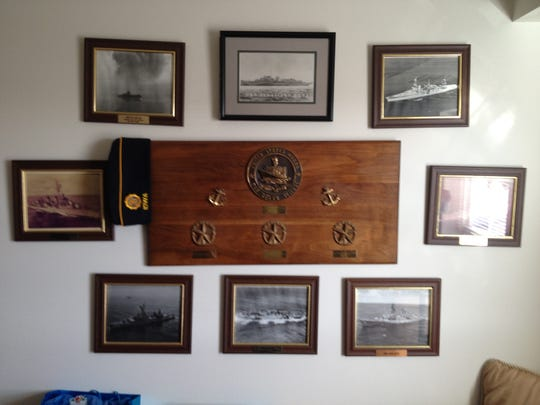 A wall in Al Sackett's home office is covered with service plaques and photos of the destroyers he served on.