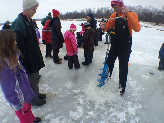 Will Downey, a volunteer for Take a Kid Outdoors, breaks the ice on frozen Sand Lake with an auger Saturday afternoon. Downey showed children how to ice fish at Iowa City's first Freeze Fest.