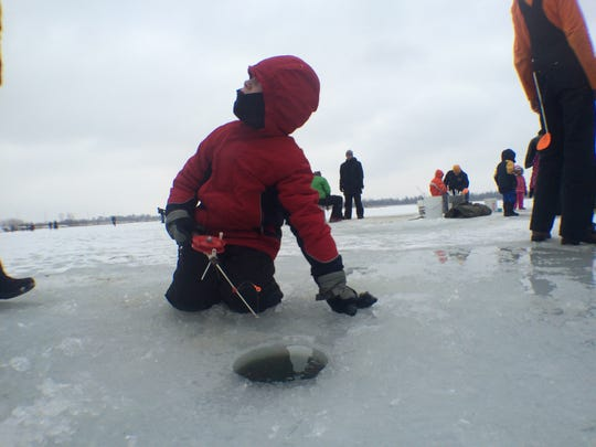 Daniel Kenyon, 7, of Iowa City looks up for advice on how to ice fish at Iowa City's first Freeze Fest at Terry Trueblood Recreation Area on Saturday afternoon.