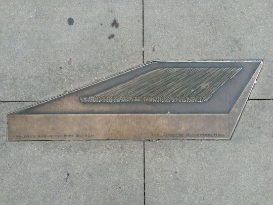 """A quote from """"The Ghost of Blackwood Hall"""" by Mildred Wirt Benson is seen along the Iowa Avenue Literary Walk in Iowa City."""