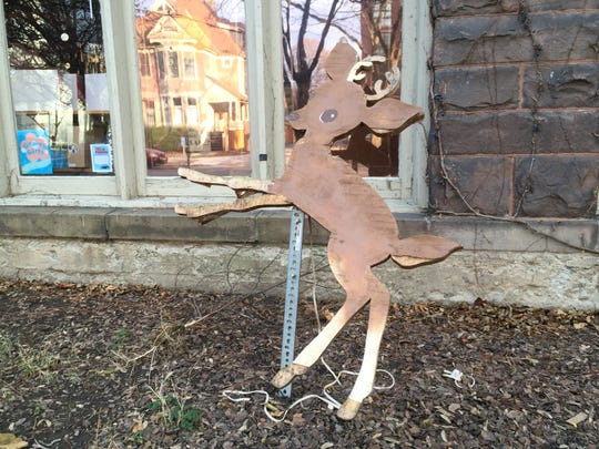 This wooden cutout of a deer commemorates the time a real deer crashed through the window of Cat's Pajamas in the Dewitt Mall in 2012.