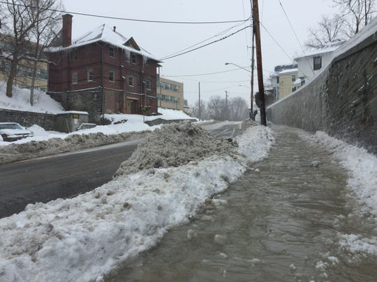 A slushy sidewalk after East Clinton and South Aurora streets were closed at 10 a.m. Sunday. A water main break had occurred at the South Aurora and Pleasant Street intersection. Emergency personnel were detouring traffic onto Hudson Street.